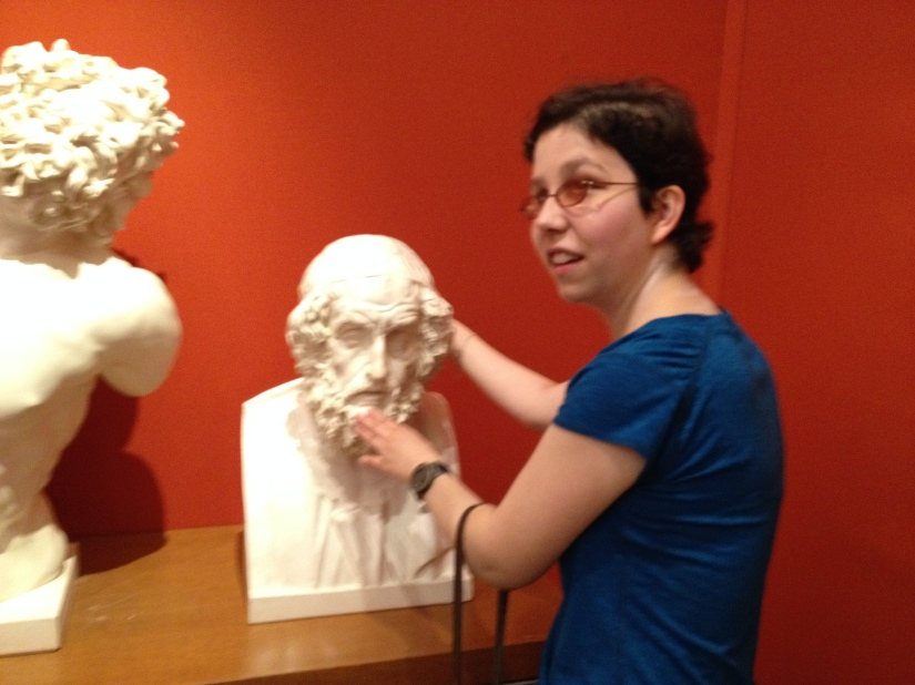 Jameyanne feeling a bust of the blind greek poet, Homer