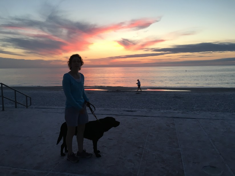 Jameyanne and Mopsy silhouetted against the sunset over the Gulf of Mexico on the beach in Pass-a-Grill Florida
