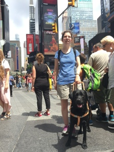 Jameyanne standing in front of a crowd in Time Square with Neutron at her side. Both person and puppy are smiling.