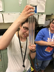 Jameyanne holding a triple-point cell for water, a glass cylinder containing solid ice, liquid water, and gaseous water vapor.
